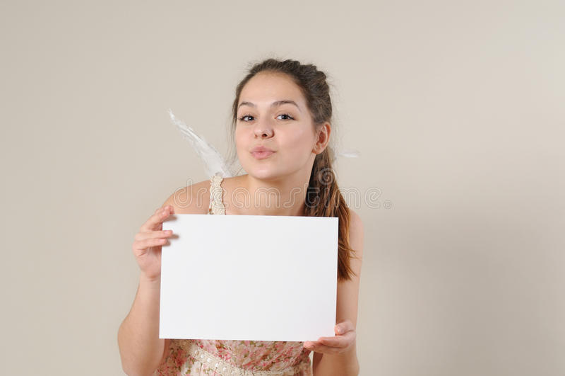 Menina bonito do anjo que funde um beijo e que guarda um cartaz vazio fotografia de stock royalty free