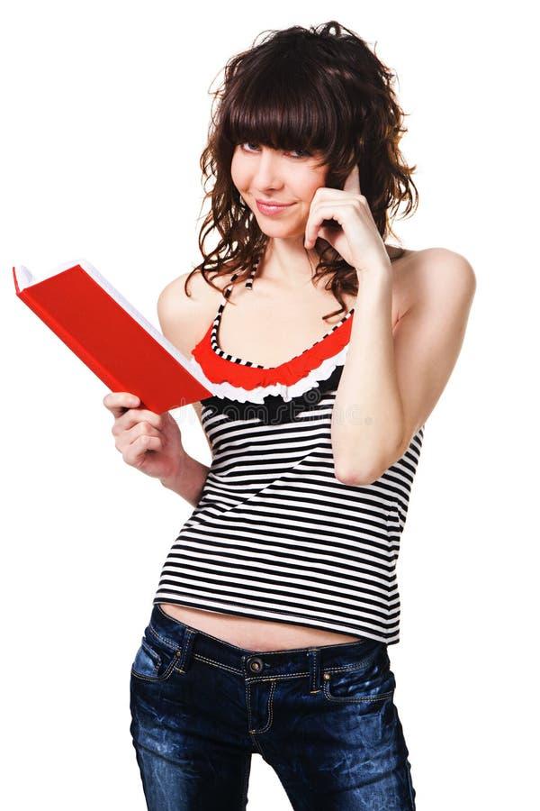 Menina bonito do estudante com um livro vermelho fotografia de stock