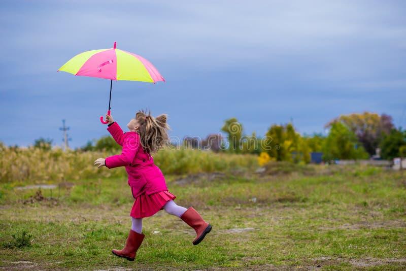 A menina bonito do guarda-chuva colorido salta engraçado ao céu fotografia de stock royalty free