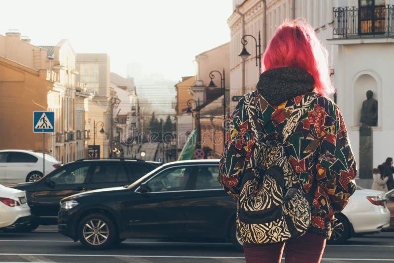 Menina bonito do moderno com cabelo cor-de-rosa, no fundo da cidade da manhã, roupa ocasional brilhante, trouxa à moda O conceito imagem de stock