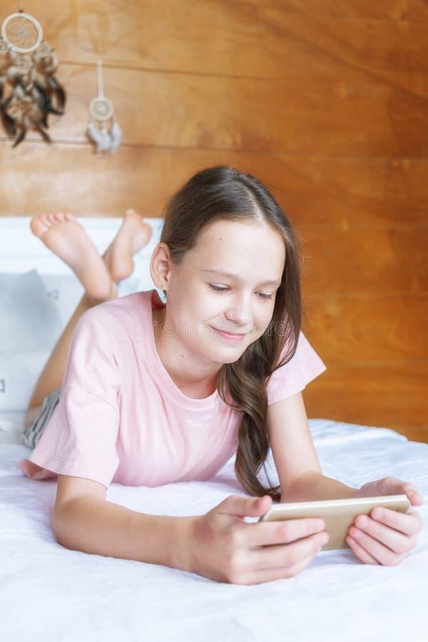 Menina bonito do preteen no t-shirt cor-de-rosa e short que encontra-se na cama com telefone celular na sala do estilo do boho co imagens de stock