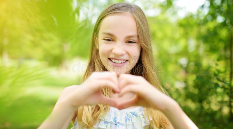 A menina bonito do preteen que ri e que guarda suas mãos em um coração dá forma no dia de verão brilhante e ensolarado Criança bo foto de stock royalty free