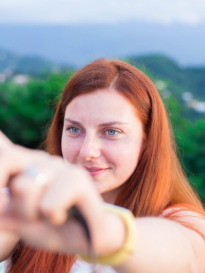 A menina bonito do ruivo toma um selfie Tem o cabelo vermelho longo, paisagens das montanhas fotografia de stock royalty free