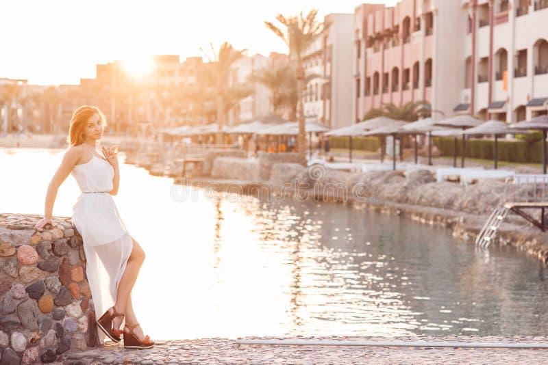 A menina bonito do ruivo vestiu-se no branco com espera cor-de-rosa dos óculos de sol foto de stock royalty free