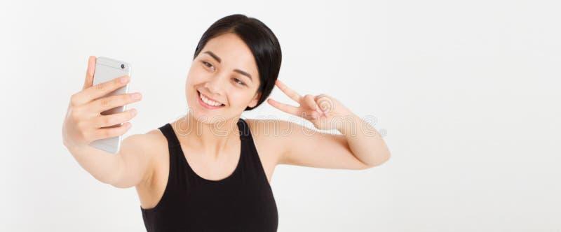 A menina bonito do sorriso moderno faz o sinal de paz dos dedos do selfie e da mostra dois foto de stock