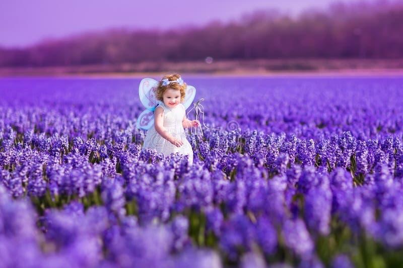 Menina bonito do toddlger no traje feericamente que joga com flores roxas