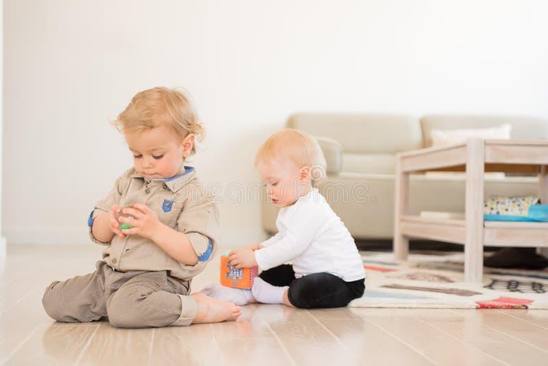 Menina bonito e menino que jogam com brinquedos em casa imagem de stock