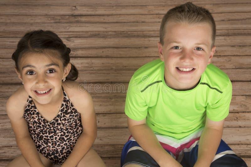 Menina bonito e menino que sentam-se em um sorriso de madeira do assoalho foto de stock