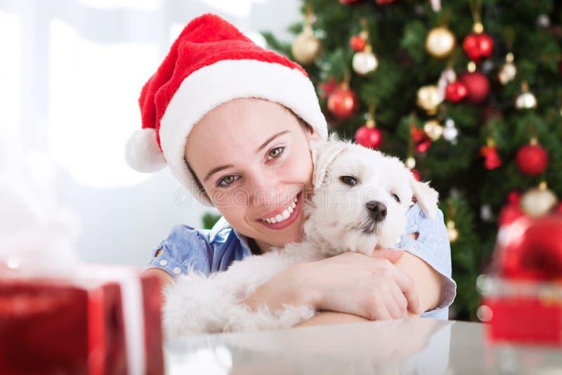 Menina bonito e seu abraço do cão e o bonito para o Natal foto de stock