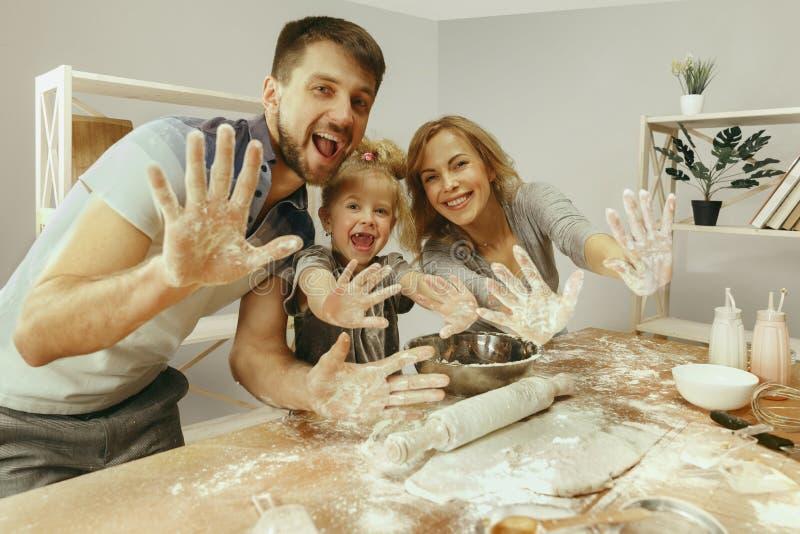 Menina bonito e seus pais bonitos que preparam a massa para o bolo na cozinha em casa imagens de stock
