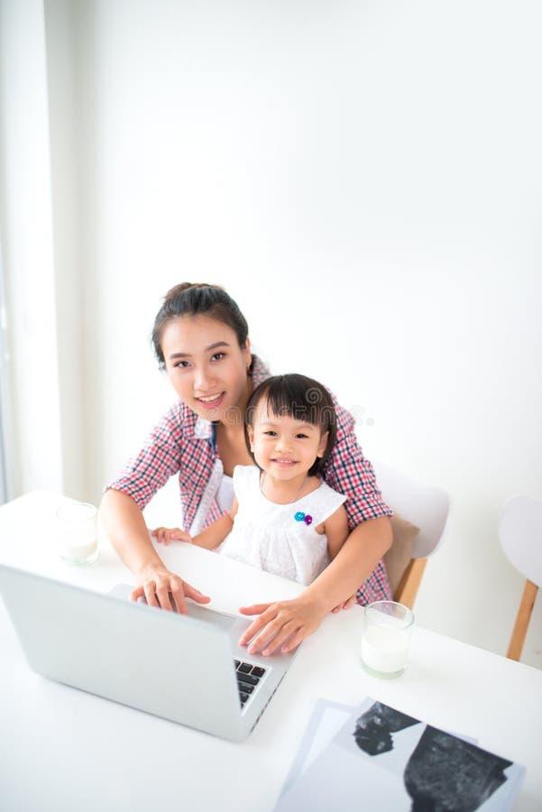 A menina bonito e sua mãe bonita estão fazendo a composição ao sentar-se no sofá em casa foto de stock royalty free