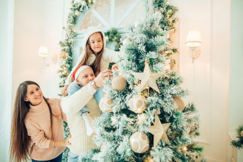 Menina bonito e sua mãe que decoram o abeto na Noite de Natal imagens de stock royalty free