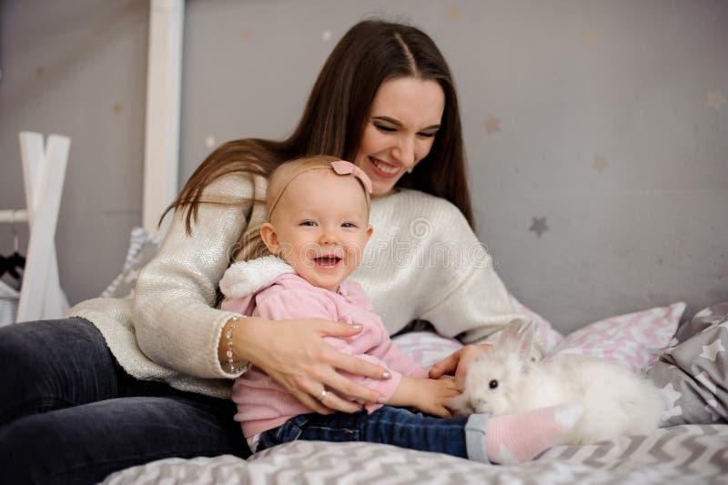 Menina bonito e sua mamã que jogam com coelho branco imagens de stock royalty free