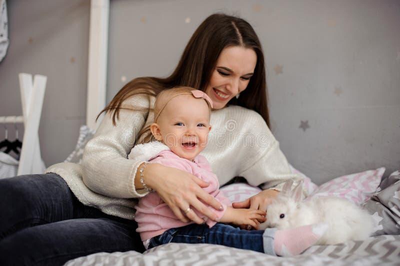 Menina bonito e sua mamã que jogam com coelho branco foto de stock