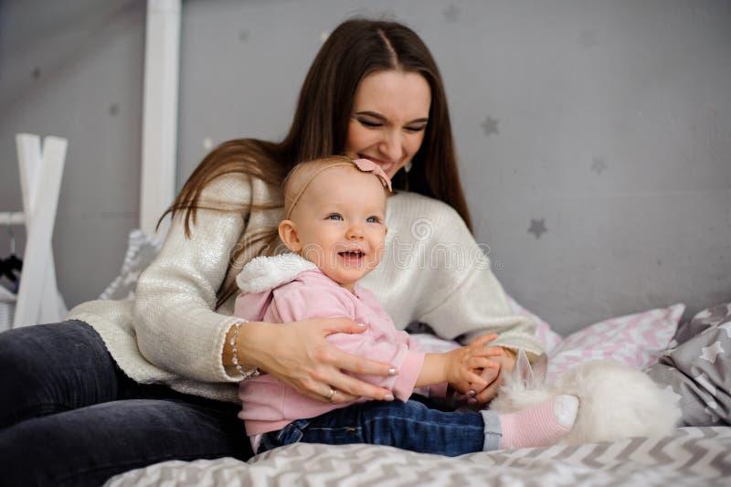 Menina bonito e sua mamã que jogam com coelho branco foto de stock royalty free