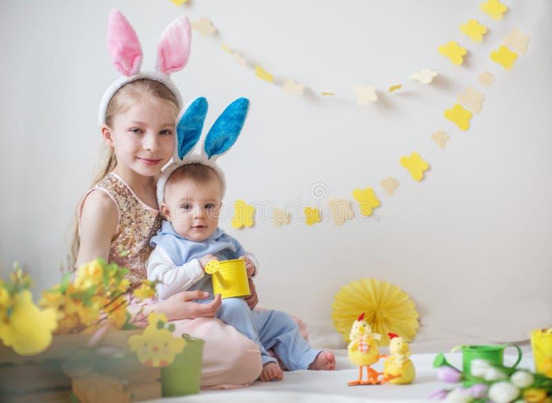 Menina bonito e suas orelhas vestindo do coelho do irmão mais novo imagens de stock