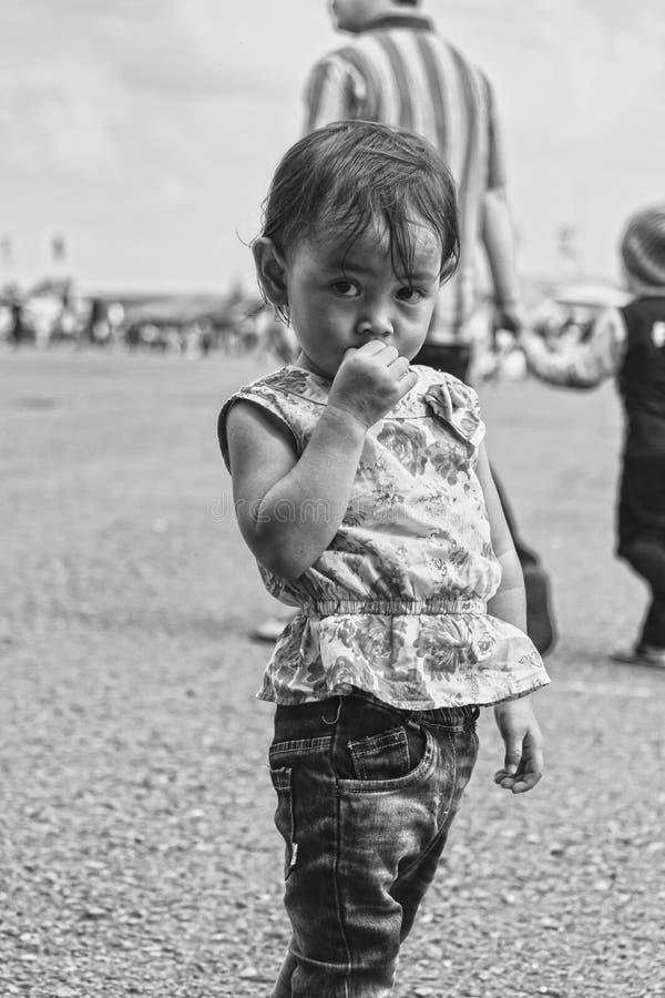 Menina bonito e tímida que olha fixamente na câmera, festival aéreo 2017 de Bandung fotografia de stock royalty free