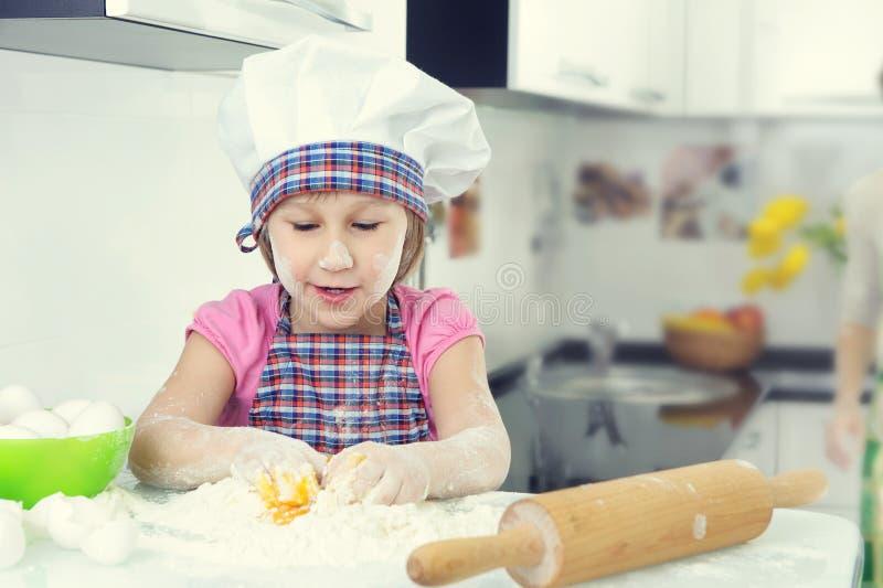 Menina bonito em cookies do cozimento do avental em casa fotografia de stock