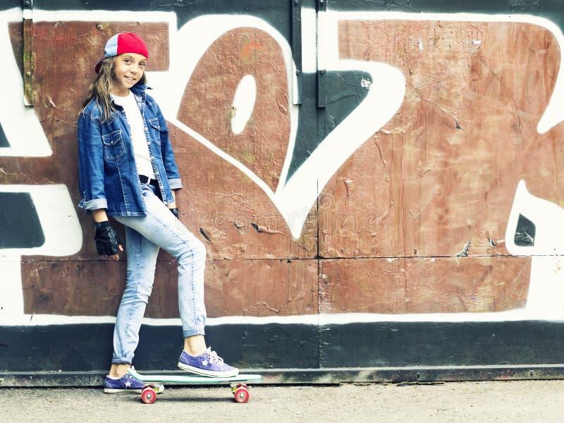 Menina bonito em um boné de beisebol com um skate em um fundo escuro esporte foto de stock