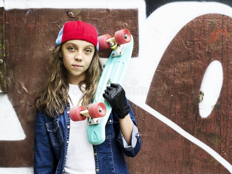 Menina bonito em um boné de beisebol com um skate em um fundo escuro esporte imagens de stock