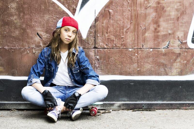 Menina bonito em um boné de beisebol com um skate em um fundo escuro esporte fotografia de stock royalty free