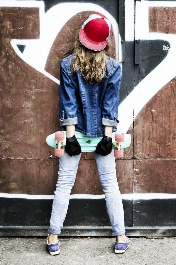 Menina bonito em um boné de beisebol com um skate em um fundo escuro esporte imagem de stock royalty free