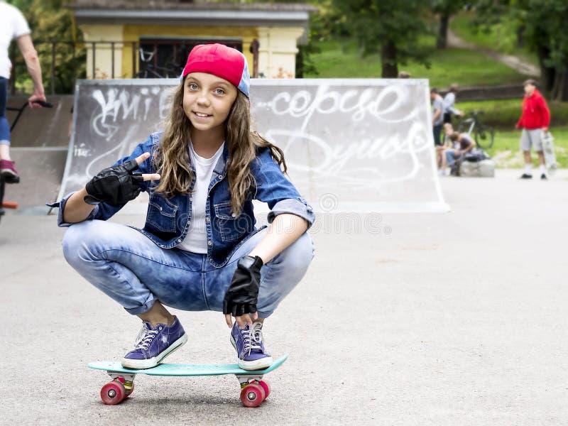 Menina bonito em um boné de beisebol com um skate em um parque do patim esportes imagem de stock