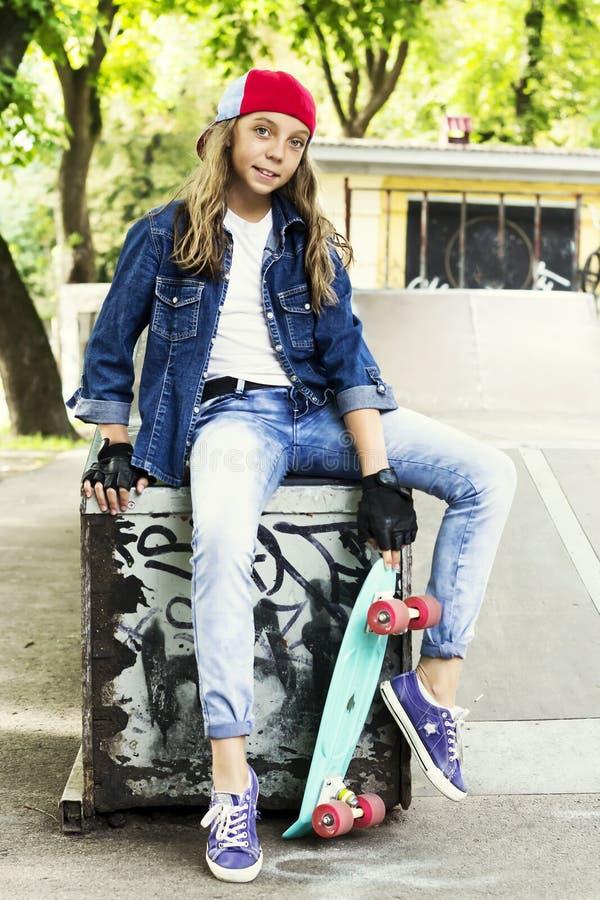 Menina bonito em um boné de beisebol com um skate em um parque do patim esportes fotos de stock