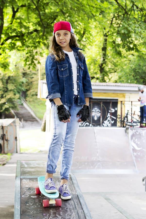 Menina bonito em um boné de beisebol com um skate em um parque do patim esportes fotos de stock royalty free