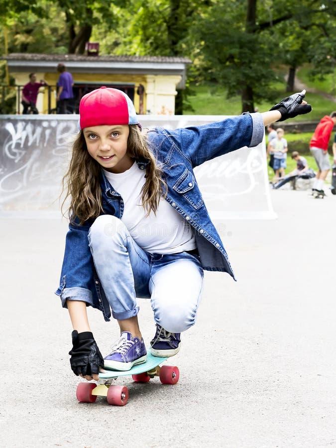 Menina bonito em um boné de beisebol com um skate em um parque do patim esportes foto de stock royalty free
