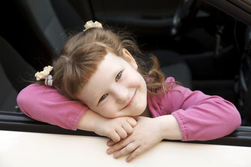 Menina bonito em um carro imagens de stock