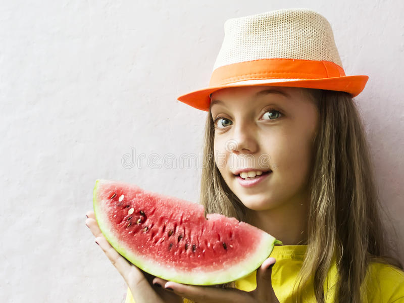 Menina bonito em um chapéu de palha com uma melancia madura fotografia de stock royalty free