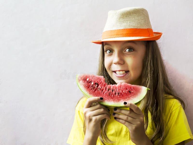 Menina bonito em um chapéu de palha com uma melancia madura foto de stock royalty free