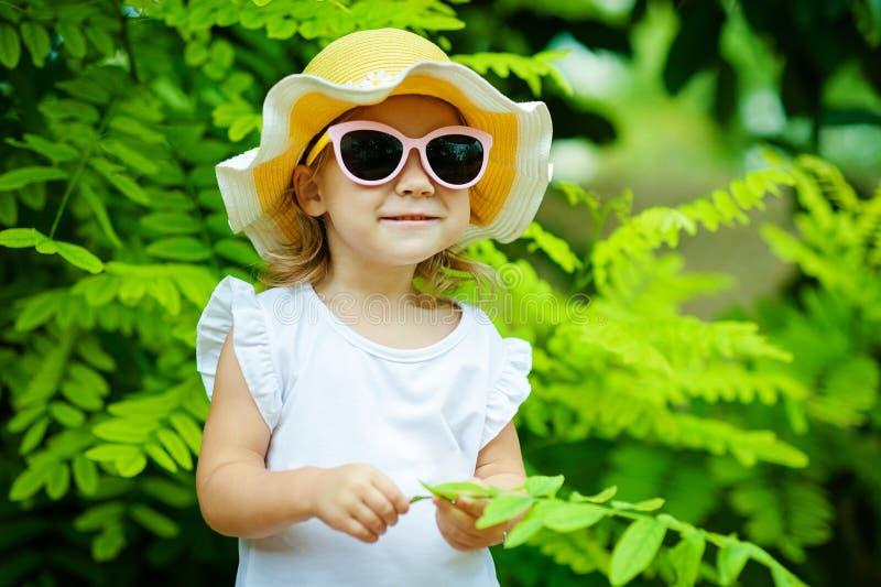 A menina bonito em um chapéu e em uns óculos de sol cor-de-rosa de palha está jogando com as folhas no parque do verão imagem de stock