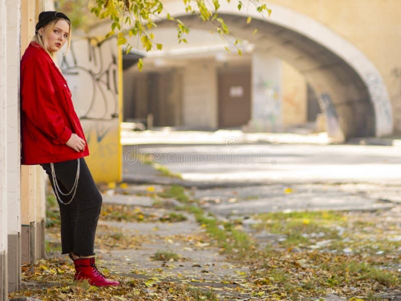 Menina bonito em um revestimento vermelho feito malha do chapéu e em umas botas vermelhas que estão perto de uma parede no cresci imagens de stock