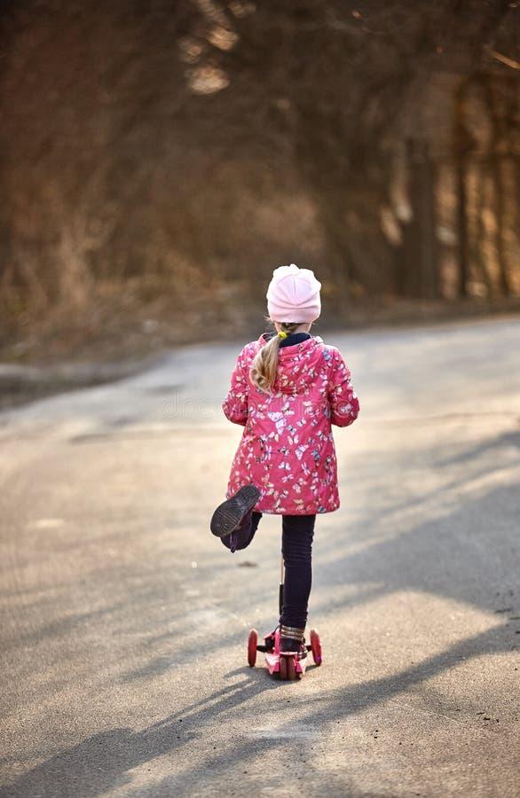 Menina bonito em um revestimento vermelho que monta um 'trotinette' abaixo da aleia fotos de stock