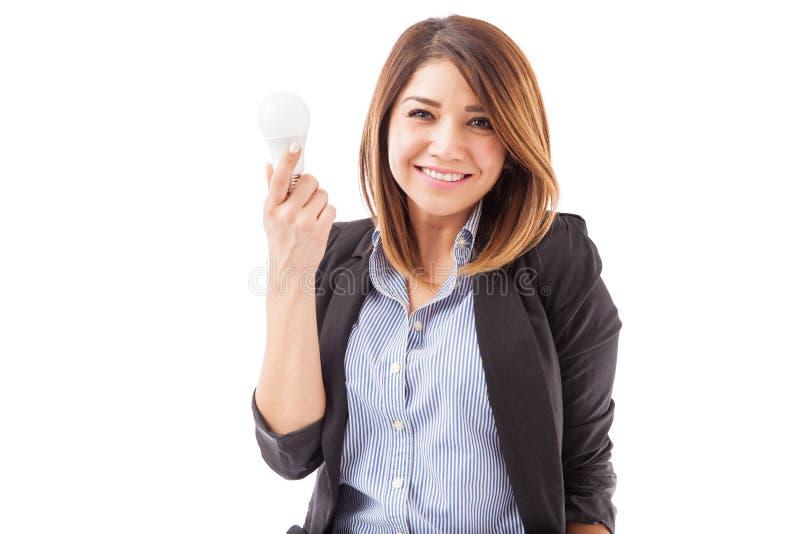 Menina bonito em um terno com uma ampola do diodo emissor de luz imagens de stock royalty free