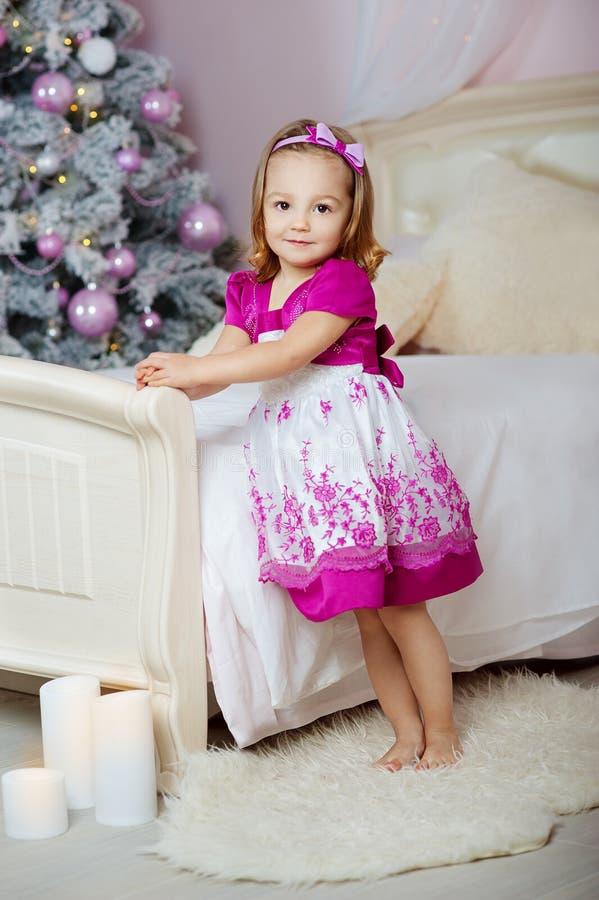 Menina bonito em um vestido cor-de-rosa que está pela cama no fundo da árvore de Natal imagem de stock royalty free