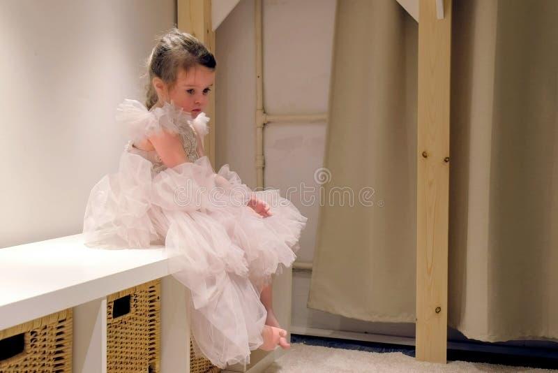 A menina bonito em um vestido bonito senta a virada em sua sala fotos de stock