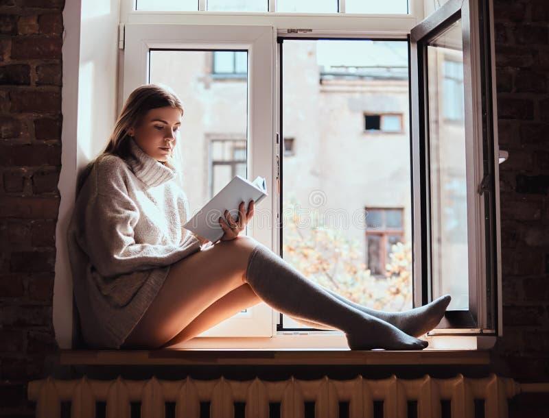 A menina bonito em uma camiseta morna e em peúgas lê um livro que senta-se no peitoril da janela ao lado da janela aberta foto de stock