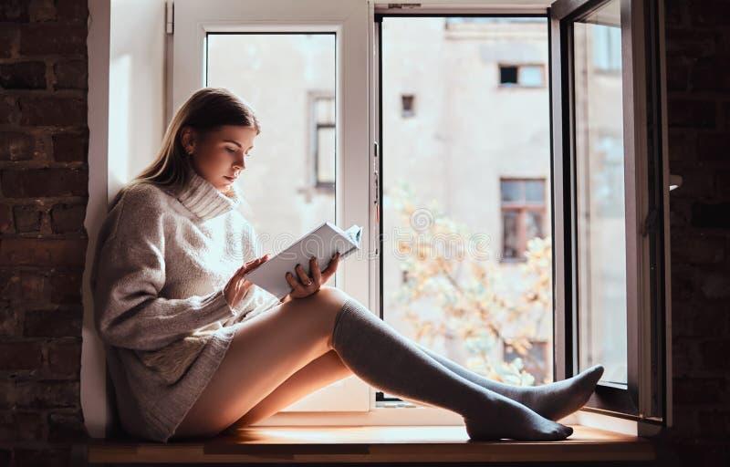 A menina bonito em uma camiseta morna e em peúgas lê um livro que senta-se no peitoril da janela ao lado da janela aberta foto de stock royalty free
