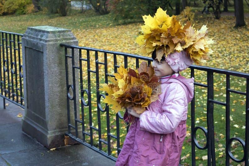 Menina bonito em uma grinalda do levantamento amarelo das folhas de bordo imagens de stock royalty free