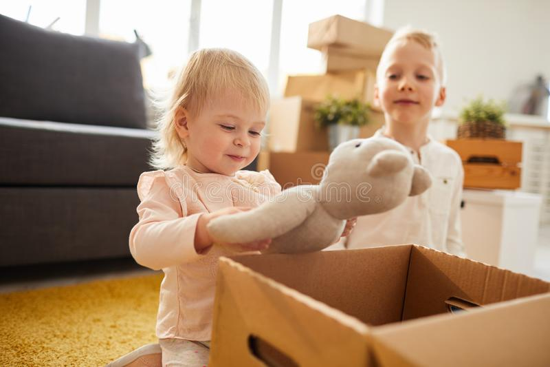 A menina bonito encontrou o brinquedo favorito na caixa fotos de stock royalty free