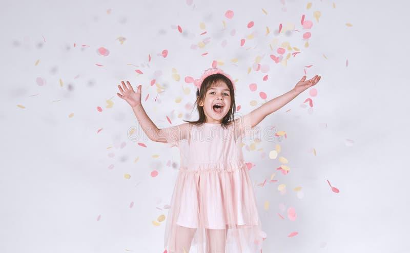 A menina bonito engraçada que veste o vestido cor-de-rosa no tule com a coroa da princesa na cabeça nas mãos brancas da elevação  imagens de stock royalty free
