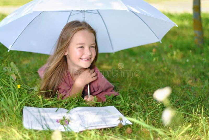 A menina bonito ensina lições na natureza no parque foto de stock royalty free