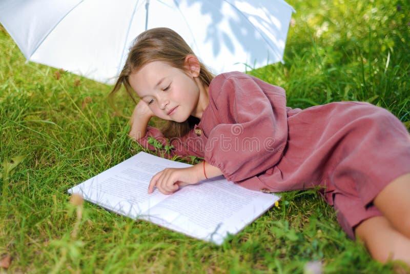 A menina bonito ensina lições na natureza no parque o bebê lê o livro imagens de stock royalty free