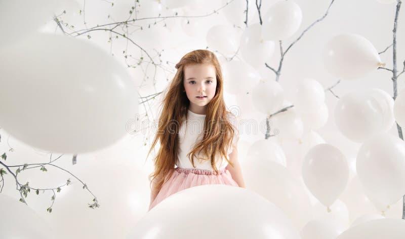 Menina bonito entre os balões brancos imagem de stock royalty free