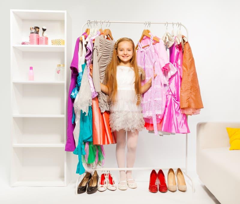 Menina bonito entre vestidos brilhantes coloridos, roupa foto de stock