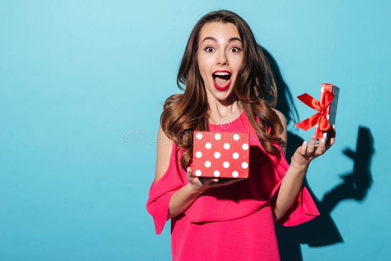 A menina bonito entusiasmado na terra arrendada do vestido abriu a caixa atual imagens de stock royalty free