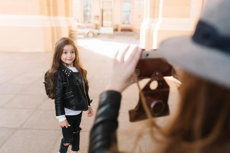Menina bonito entusiasmado no equipamento do estilo da rocha que levanta com expressão bonita para sua mamã, chapéu na moda vesti foto de stock royalty free